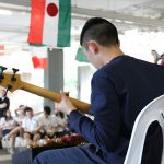 Student playing guitar outside