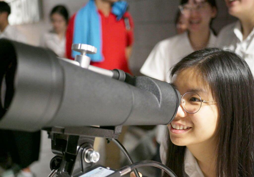 Student looks through telescope